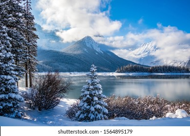 Landscaper view of a snowy shoreline against an unfrozen cold steamy lake with mountains in the background on a sunny day.