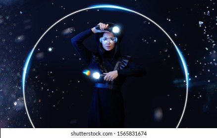 Beautiful woman in futuristic dress over dark magic background. Gamer girl in glasses of virtual reality with controllers in hands. Augmented reality, game, hobby concept. VR. Blue neon light.