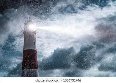 Gran faro rojo y blanco en una noche llena de lluvia y tormenta con un haz de luz que brilla en el mar