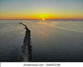 Vista aérea de drone de un largo rompeolas y puesta de sol