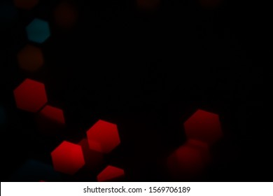 Hexagonal red and blue bokeh lights on dark background from unfocused macro created with a vintage lens.