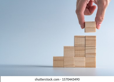 階段の形として木製の立方体の積み重ねを手で配置し、シンボルやロゴを作成するためのモックアップ、ビジネスの成長と管理の概念