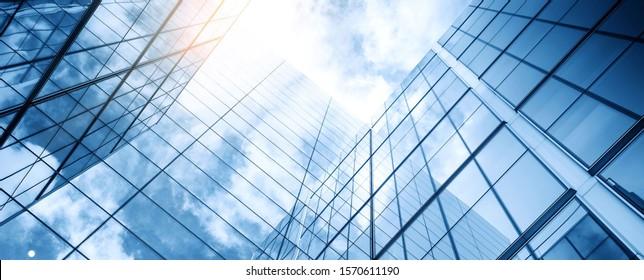 曇った青い空を背景にガラスの建物
