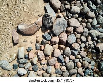 Las olas del mar azotan la roca de impacto en la playa. Fondo de rocas