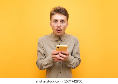 Surprised guy in glasses and mustache is standing on yellow background with smartphone in hands and looking into the camera.Portrait of surprised batman using smartphone isolated on yellow background