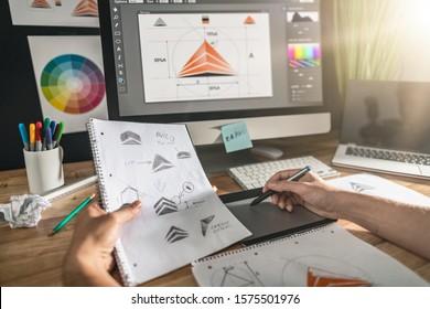 Grafikdesignerzeichnung skizziert Logoentwurf. Das Konzept einer neuen Marke. Professionelle kreative Beschäftigung mit Idee.