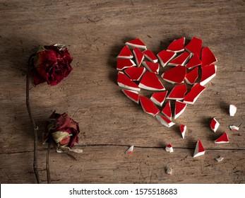 Gebrochenes Herz mit gebrochenem rotem Glas und roter Rose trocken auf Holzhintergrund, um meinen Herzhintergrund zu brechen. Begleitender Traurigkeitsartikel. Herzpaar oder Herzplakat.