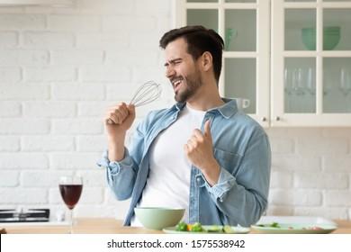 Chico divertido cantando canción con batidor batidor micrófono escuchando música en la cocina moderna, feliz alegre joven divirtiéndose cocina bailando preparando cena saludable comida bebida vino solo en casa