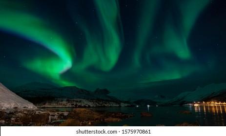 grüne Aurora Borealis am Rande des Meeres mit Schimmern von Städten in einer verschneiten Landschaft und scharfen Bergen