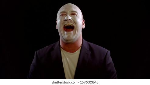 Mann mit weißem Make-up im Gesicht lacht wie ein Witzbold im schwarzen Hintergrund, böses unkontrollierbares Lachen