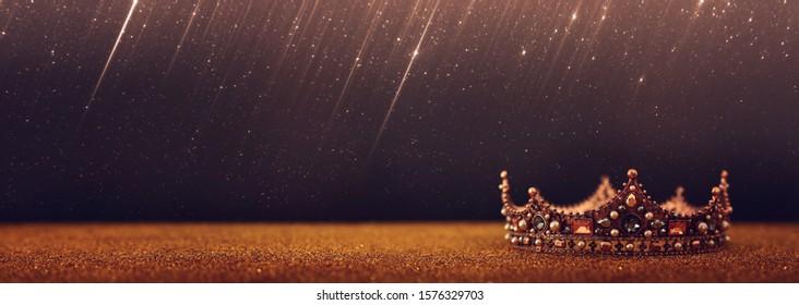 zurückhaltendes Bild der schönen Königin / Königskrone über Goldglitzertisch. Vintage gefiltert. Fantasie Mittelalter