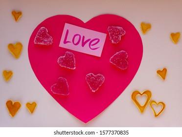 バレンティンの日。マーマレードハート、甘いお菓子、パステル調の背景にオレンジの皮の心を乾燥させます。愛、上面図、フラットレイアウト。