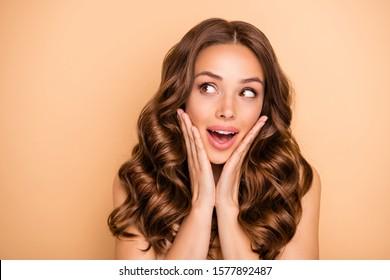 ベージュのパステルカラーの背景に分離された素敵な魅力的な素敵なフェミニンな官能的なゴージャスな陽気な陽気な女の子らしいウェーブのかかった髪の女の子が期待して販売を楽しんでいるのクローズアップの肖像画