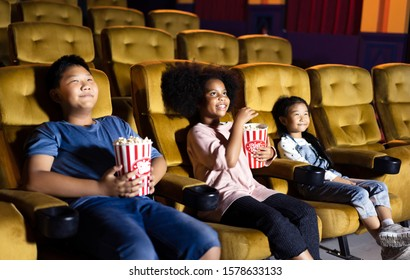 Kid group see movie in theater with friends. They eat a popcorn and funny with big smile. Multiplex with yellow seat.