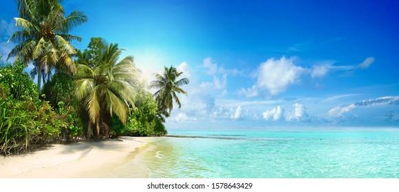 Schöner tropischer Strand mit weißem Sand, Palmen, türkisfarbenem Ozean gegen blauen Himmel mit Wolken am sonnigen Sommertag. Perfekter Landschaftshintergrund für erholsamen Urlaub, Insel Malediven.