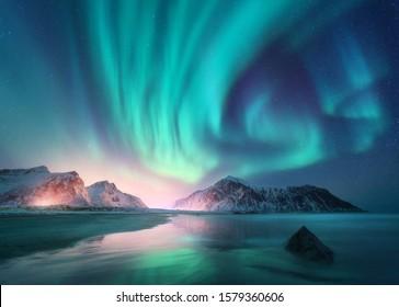 Polarna svetlost nad morjem, zasneženimi gorami in mestnimi lučmi ponoči. Severni sij na otokih Lofoten na Norveškem. Zvezdno nebo s polarnimi lučmi. Zimska pokrajina z auroro, odsevom, peščena plaža