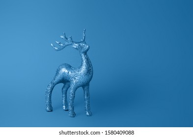 Sparkling deer decoration for Christmas. Deer figurine isolated on blue background. Christmas symbol. Decorations deer. Silver glitter stag decoration. Color of the year 2020 classic blue.