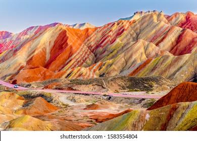 Erstaunliche Landschaft des Regenbogenberges und des blauen Himmelshintergrundes im Sonnenuntergang. Zhangye Danxia National Geopark, Gansu, China. Bunte Landschaft, Regenbogenhügel, ungewöhnlich farbige Felsen, Sandsteinerosion