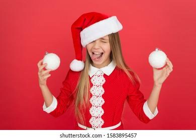 新年が来るので、お祝いを続けてください。クリスマスと新年を祝う幸せな女の子。小さな子供は冬休みを祝うのを楽しんでいます。お祝いの時間。サンタスタイルで祝います。