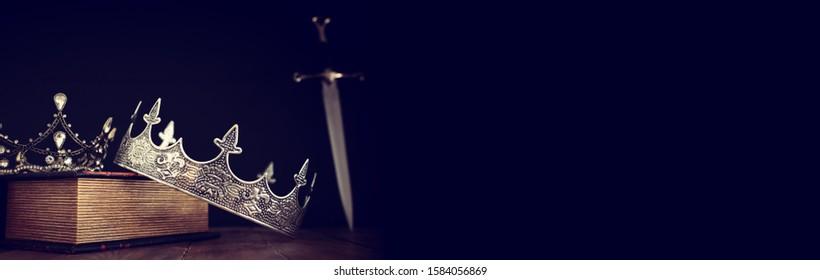 rustig beeld van mooie koningin / koningskroon over antiek boek naast zwaard. fantasie middeleeuwse periode. Selectieve aandacht