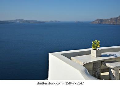 Traditionelle Hausveranda mit einem handgefertigten Gips-Tisch und Hockern aus Elfenbein und einem Miniaturorangenbaum mit Blick auf die Caldera auf der Insel Oia Santorini, Kykladen, Griechenland.