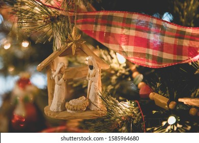 Closeup of Christmas Nativity Ornament with Joseph, Mary and Baby Jesus on Christmas tree with plaid ribbon and wooden beads