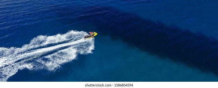 Ultraweites Foto der Luftdrohne von Jet-Ski-Wasserfahrzeugen, die mit hoher Geschwindigkeit auf einer tropischen exotischen Insel kreuzen