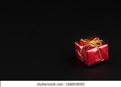 Regalo de Navidad tmass en papel rojo aislado en fondo negro