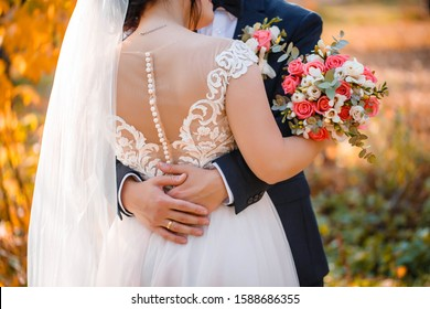 Petite bride in buttons back and butterfly back, pink powder color wedding dress is holding wedding bouquet with  pink  roses, the groom's arm around her waist, back view