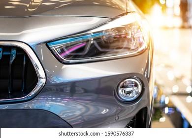 Modern, shiny SUV headlight in a car showroom.