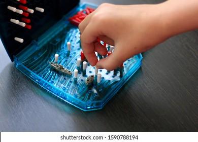 Mädchen spielt im Brettspiel Schlachtschiff, Spielzeugkriegsschiffe und U-Boot. Selektiver Fokus.