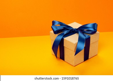 Trendy attractive minimalistic gift with blue bow on the orange background. Merry Christmas, St. Valentine's Day, Happy Birthday and other holidays concept. Copy space.