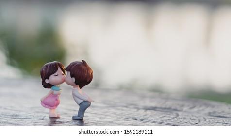 Pareja de muñecas enamoradas beso romántico con fondo de naturaleza y luz solar, concepto de día de San Valentín, enfoque selectivo.