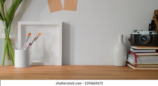Nahaufnahme des bequemen Designerarbeitsplatzes mit Büromaterial und Kopierraum auf Holztisch