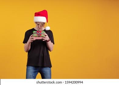 赤いサンタの帽子をかぶった若い男は彼の手でギフトボックスを保持し、黄色の背景にポーズをとる