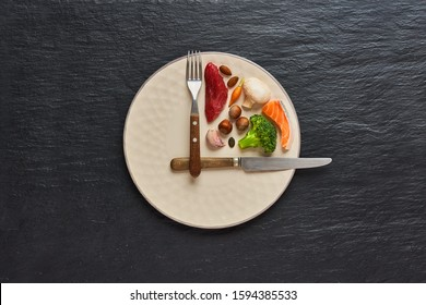 20:4 fasting diet concept. One third plate with healthy food and two third plate is empty. Beef, salmon, egg, broccoli, tomato, nuts, carrots, mushrooms. Dark background. Top view.