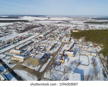 Aerial view of Oktyabrski village with administration building, school, forest and roads. Russia. Winter, sunny