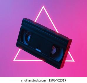 Minimalismus Retro-Stil-Konzept. 80er Jahre. Videokassette in neonrotem blauem Licht. Retro Welle. Pop-Art