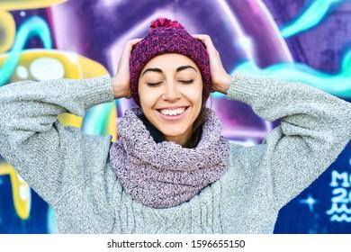 都市の背景に対して目を閉じてポーズをとって笑顔の女性のクローズアップ屋外の肖像画。暖かいセーター、ニットのスカーフ、帽子を身に着けています。アーバンウェアスタイル、ストリートスタイル、ライフスタイルポートレート。