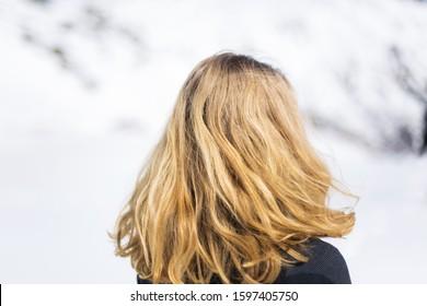 Rückansicht eines jungen Mädchens. Frau mit schönen goldenen Haaren der dunkelblonden Farbe. Person, die auf frischem weißem Schnee steht. Reflexionen, die Sonne scheint auf ihre Haare. Im Hintergrund weiße Alpenberge.