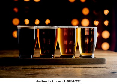 Beer flight. Traditional classical American diner or bar drink item, with variety of beers for tasting. IPA, wheat beer, porter, pilsner, pale ale, stout. Lined up on the bar at a restaurant.