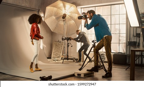 Behind the Scenes on Photo Shoot: Beautiful Black Model Posing for a Photographer, he Takes Photos with Professional Camera. Stylish Fashion Magazine Photoshoot with Pro Equipment in a Studio