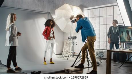 写真撮影の舞台裏:写真家のための美しい黒いモデルのポーズ、彼はプロのカメラで写真を撮ります。スタジオでプロの機器を使って行われたスタイリッシュなファッション雑誌の写真撮影
