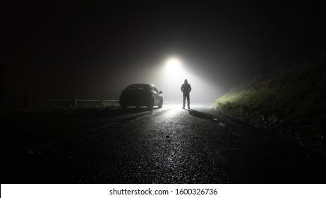 Un automóvil solitario, estacionado a un costado de la carretera, debajo de una farola, con una figura encapuchada, en un camino rural espeluznante, aterrador, rural. En una noche de invierno brumoso
