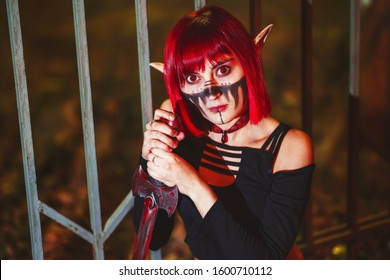 Girl cosplay in the image of a dark elf in a red wig portrait close-up. A woman with red lenses in her eyes and red hair in an elf costume with false ears and makeup. Dark elf outfit for Halloween.