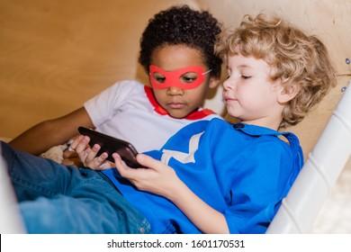 Zwei kleine interkulturelle erholsame Jungen in Kostümen von Superman, die Bildschirm des Smartphones betrachten, während sie sich zur freien Verfügung entspannen