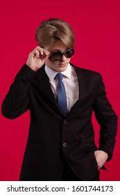 赤い背景にポーズをとって黒いジャケット、ネクタイ、サングラスの若いティーンエイジャーの男