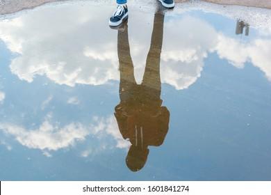 真っ青な空に立っているカジュアルなスタイルの男の水の反射