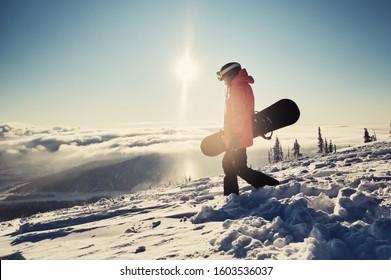 山の斜面に立ってスノーボードを保持し、スノーボードの準備をしている女性スノーボーダー。スキーリゾートの晴れた冬の日