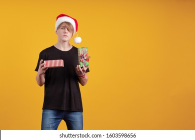 Young guy in a red santa hat holds a gift box in his hands and poses on a yellow background